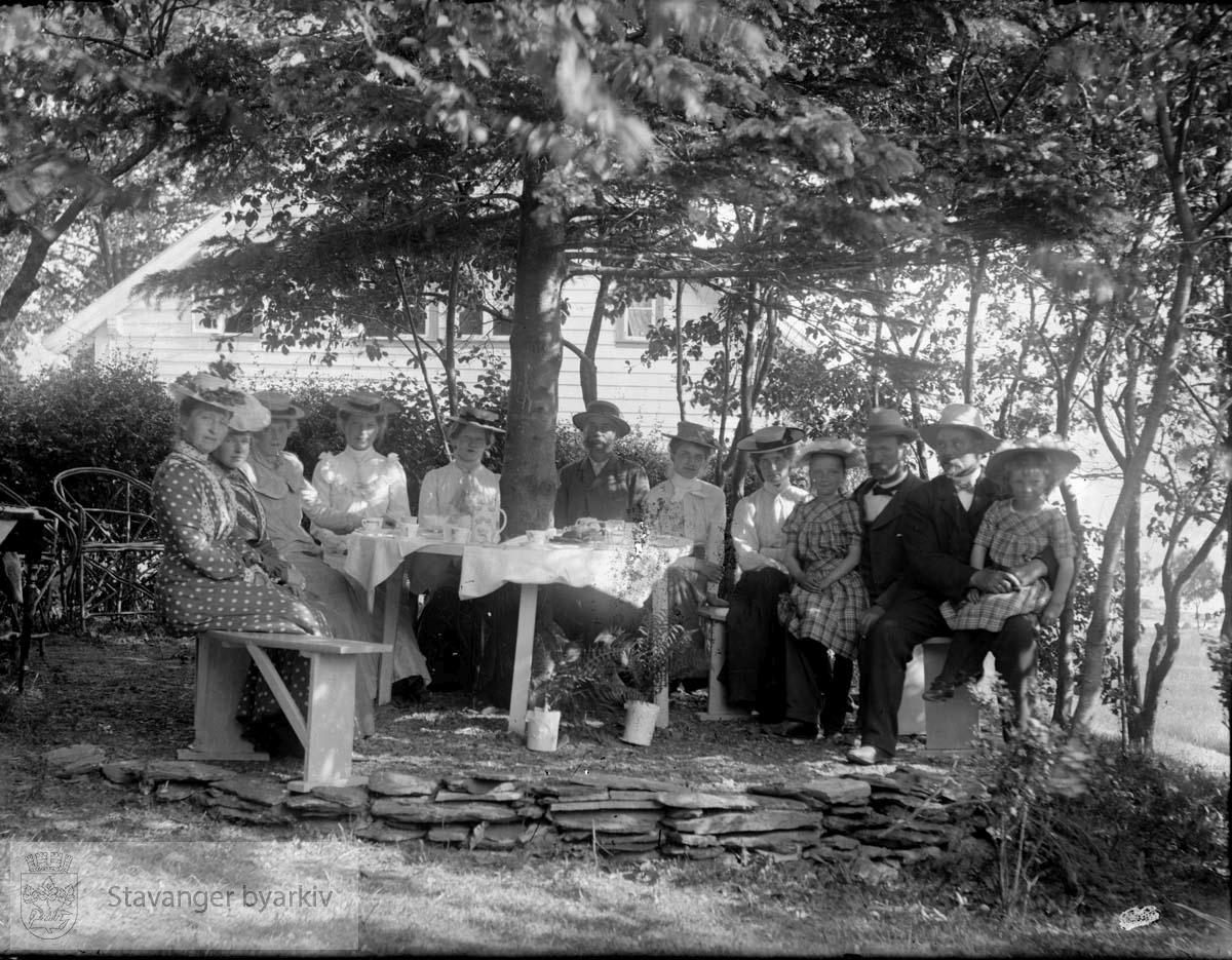 """Konsul Chr. Bjelland med familie på besøk hos skipsfører Weidemann Olsen på hans landsted """"Sjøheim"""" på Stord. Her nytes ettermiddagskaffen i hagen en sommerdag i 1902. (Se Minneboken om Stavanger, s. 266)"""