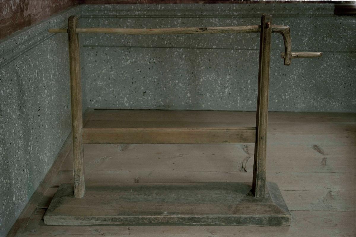 Bobinställning (a) av barrträ, bestående av en bottenplatta med två upprättstående ståndare med tvärslå på mitten, vev (b) .