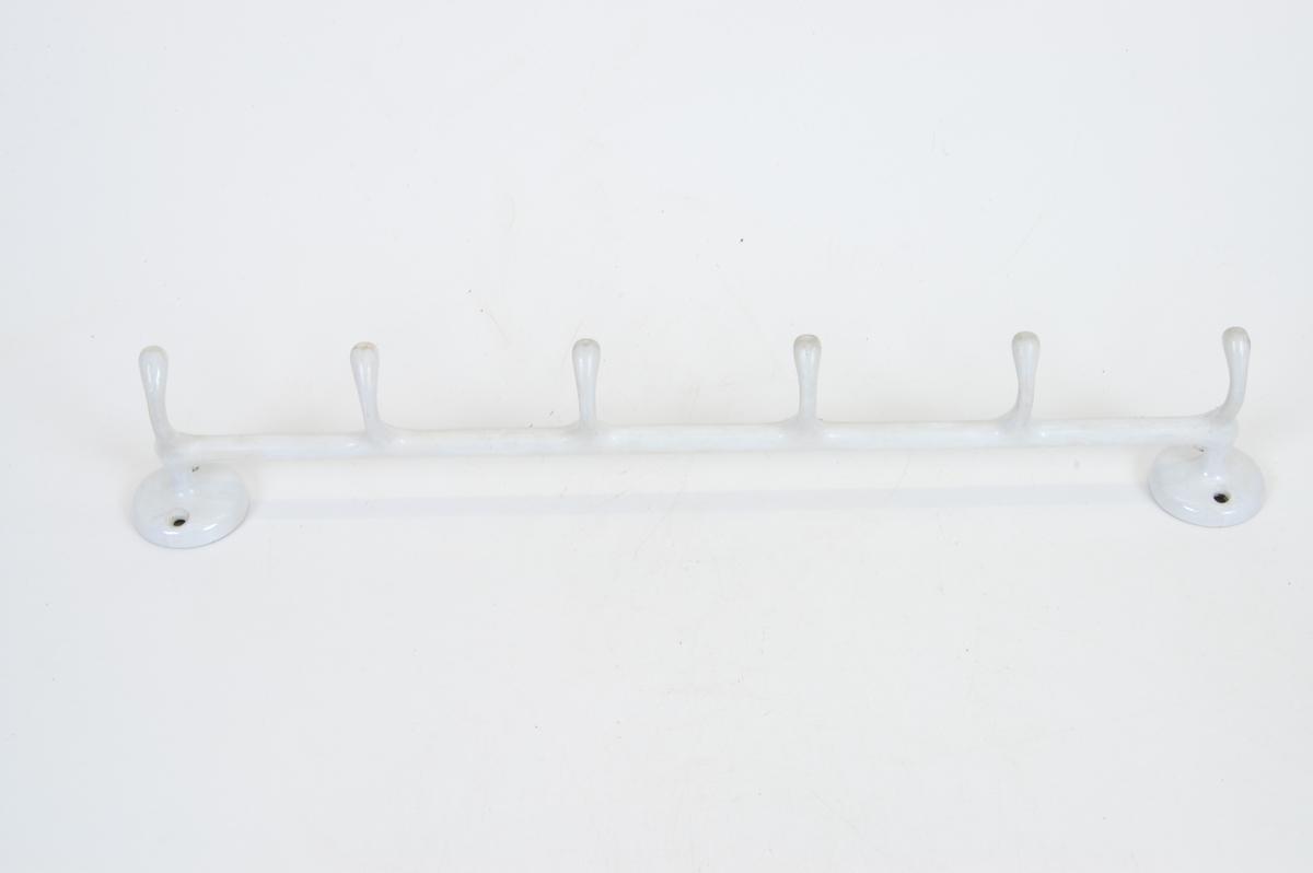 Form: lang stang med 6 buede utvekster o festet til veggen med to runde fester med to hull for skruer i hver.