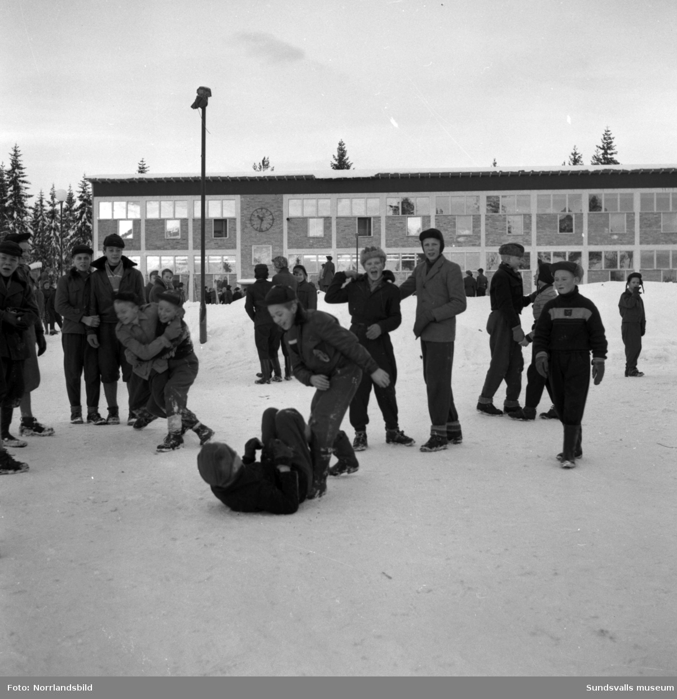 Vintriga utomhusbilder med barn på Hagaskolan, rastlek och skidåkning.