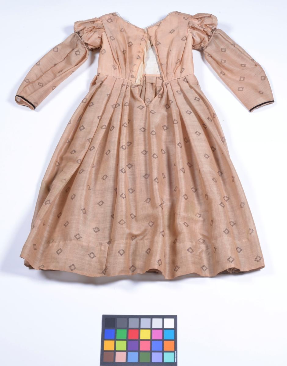 Ljusbrun barége. Till klänningen användes hemstickade strumpor och svarta snörkängor.  Sydd av Augusta Welin på sin tid stadens storsömmerska.