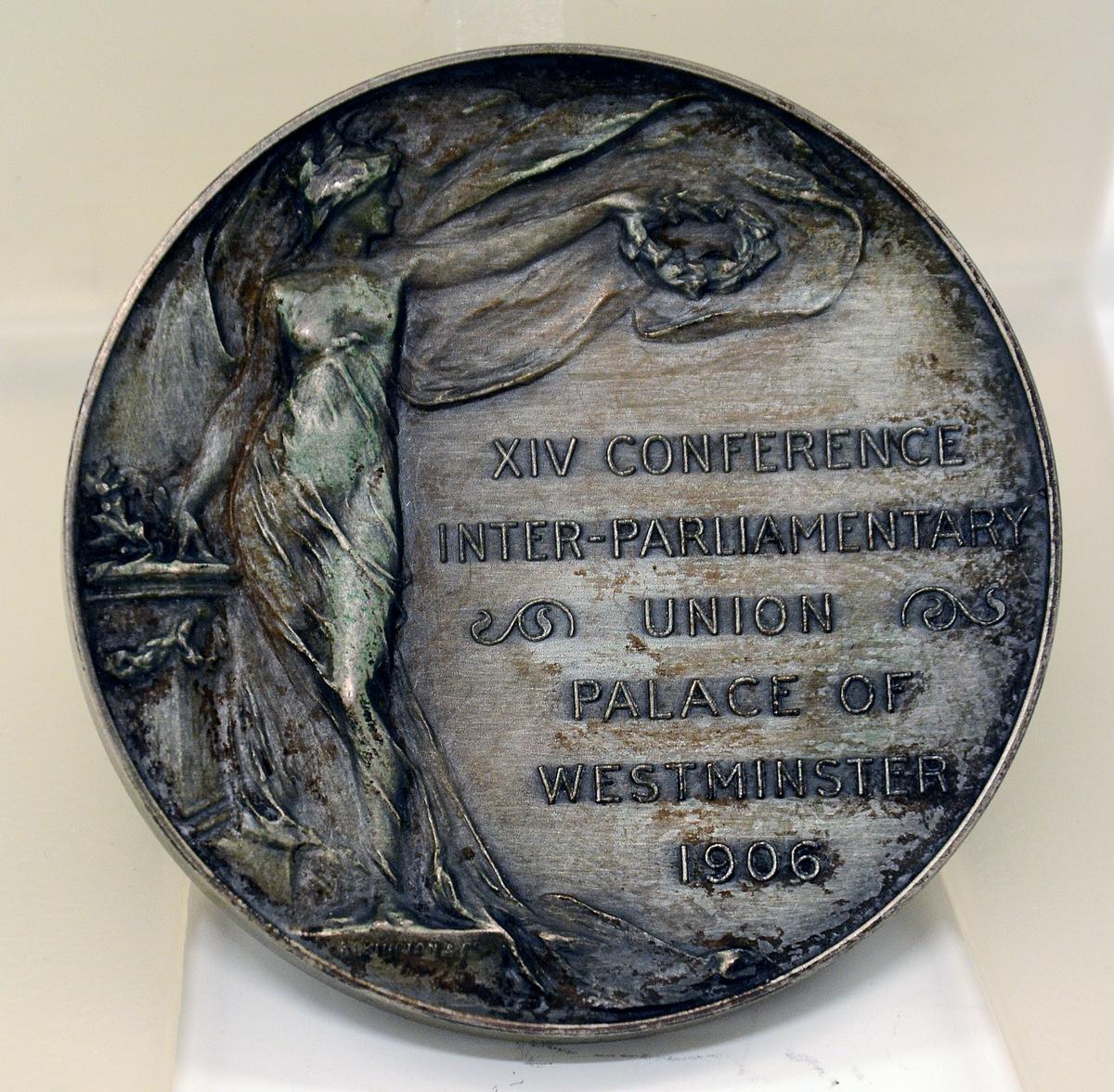 Minnemedalje i etui. Sirkelrund i metall. På den ene siden portrett av Edvard VII av England samt tekst: KING EDVARD VII THE PEACEMAKER. Under portrettet av Edvard teksten: A.WYON SC. På den andre siden bilde av gudinne og tekst: XIV CONFERENCE INTER-PARLIAMENTARY UNION PALACE OF WESTMINSTER 1906. Sirkelrundt, rødt etui med gullbokstaver: INTER-PARLIAMENTARY CONFERENCE LONDON 1906. Innvendig hvit silke i lokket med gullbokstaver: WYON 237 Regent Street W. Blå fløyel i bunnen og blått silkebånd. Metallåpner og hengsle.
