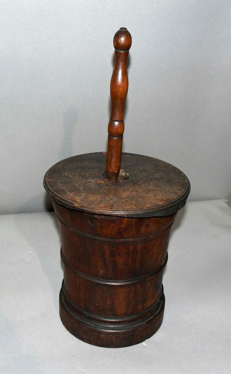 Sylinderformet morter med profilerte linjer i tverrsnitt. På den øverste kant er det et hakk i morteren. Omtrent halvparten av kanten på lokket er avknekt. Staven er profilert.