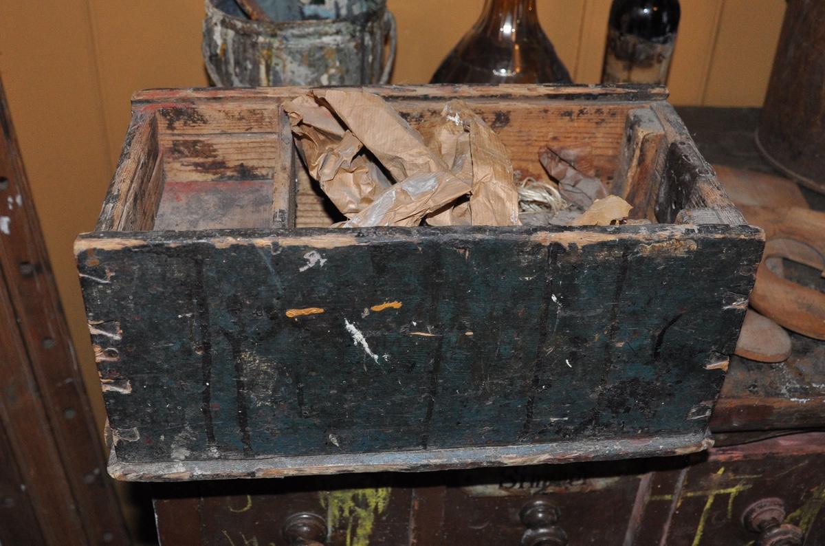 Rektangulær kasse av tre, med skyvelokk som mangler. Kassen har en seksjon på den en siden. Malt grønn på utsiden.