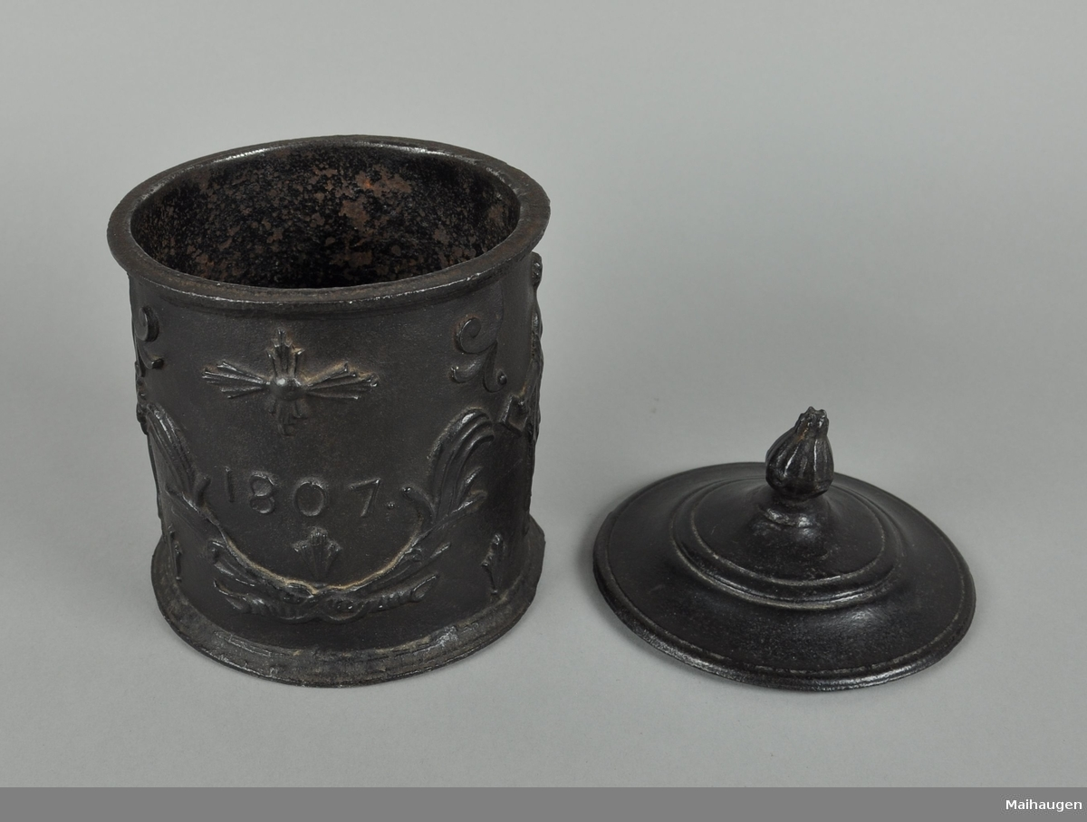 Tobakksdåse av støpejern. Rund form med lokk. Profilert dekor med motiv av girlandere og mennesker i antikke klær.