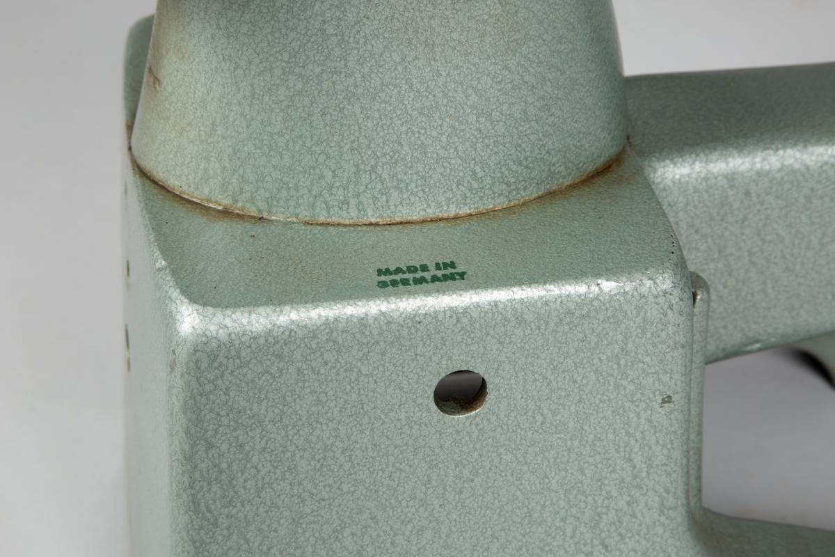 Skomakersymaskin, type Adler med stativ  Stativet er utført i metall, samme grønnfarge som maskinen.  Har innebygd støtte for beina.  Høyde: 67 cm Bredde: 50 cm Lengden: 84 cm