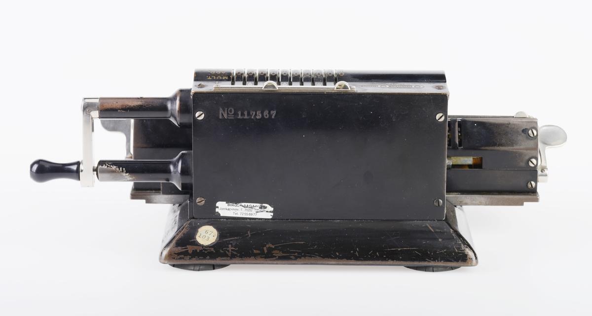 """Hånddrevet regnemaskin som utfører summering, subtraksjon, divisjon og multiplikasjon (markert til høyre på maskinen). Den er laget av svartlakkert metall, og den står på fire runde gummiføtter. Bokstaver og tall er gullfarget, bortsett fra modellnummeret på undersiden. Det er påført både primær og sekundær tekst, se """"Påført tekst/merker"""".  Inntasting skjer ved hjelp av innstillingstenger på 10 tallrekker fra 0-9 øverst på maskinen. Maskinen driftes ved hjelp av en håndsveiv på høyre side. Den har 13 siffer i resultatviseren (til høyre på fronten)."""