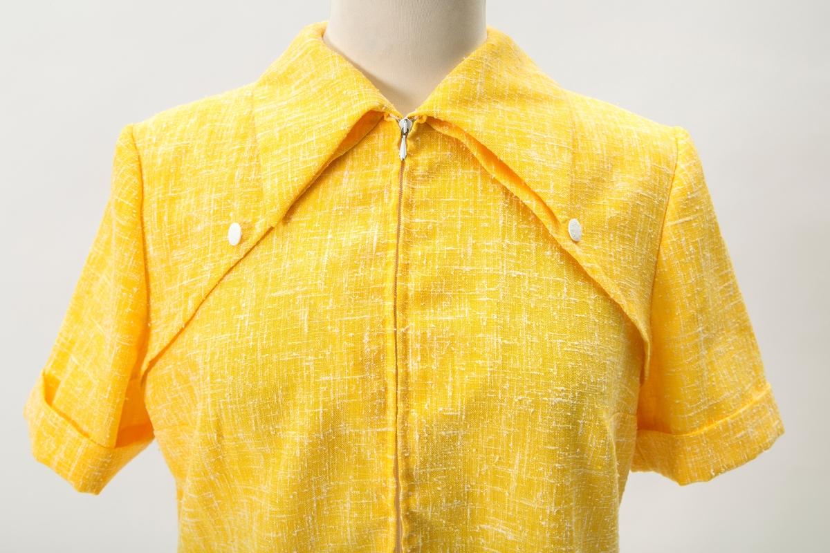"""Ensfarget gul kjole fra slutten av 60 tallet. Korte ermer. En lomme med lilla og grønt blomst. Glidelås foran. To hvite knapper med stjerner på kragen. En på baksiden.  """"Kjoler fra slutten av 1960 tallet. Etter jeg begynte å jobbe i 1968. Helt klassiske for hva som var moderne på den tiden. Husker at kjolene er fra min tid i Oslo. Desverre finnes det ikke bilder av meg med disse klærne."""" Tidligere eier"""