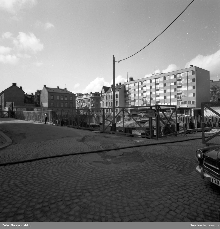 Den nya genomfartsleden i före detta järnvägsparken är nyasfalterad. Mot Strandgatan plank och byggbaracker för bygget av Strand hotell i kvarteret Neptunus.