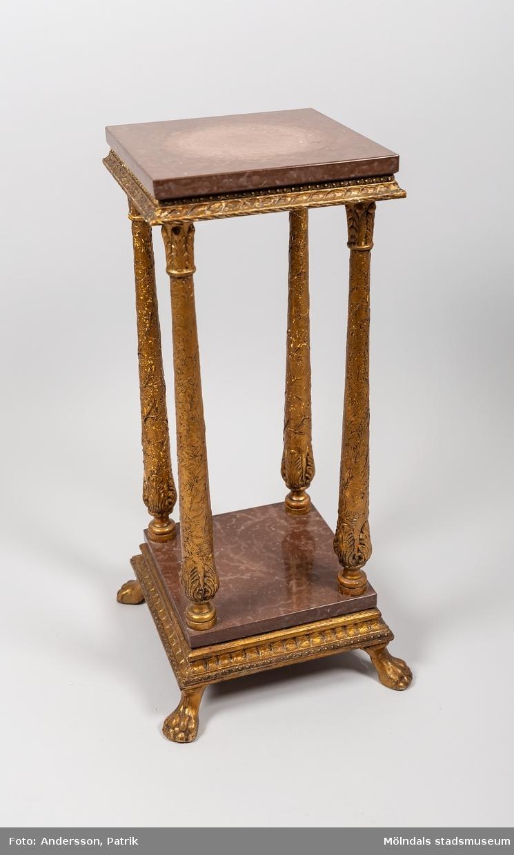 Piedestal från 1920-talet.  Piedestalen är tillverkad av förgyllt trä med rödbruna marmorskivor. Den har fyra stycken rikt utsmyckade ben och står på fyra lejontassar, som också är tillverkade av förgyllt trä.