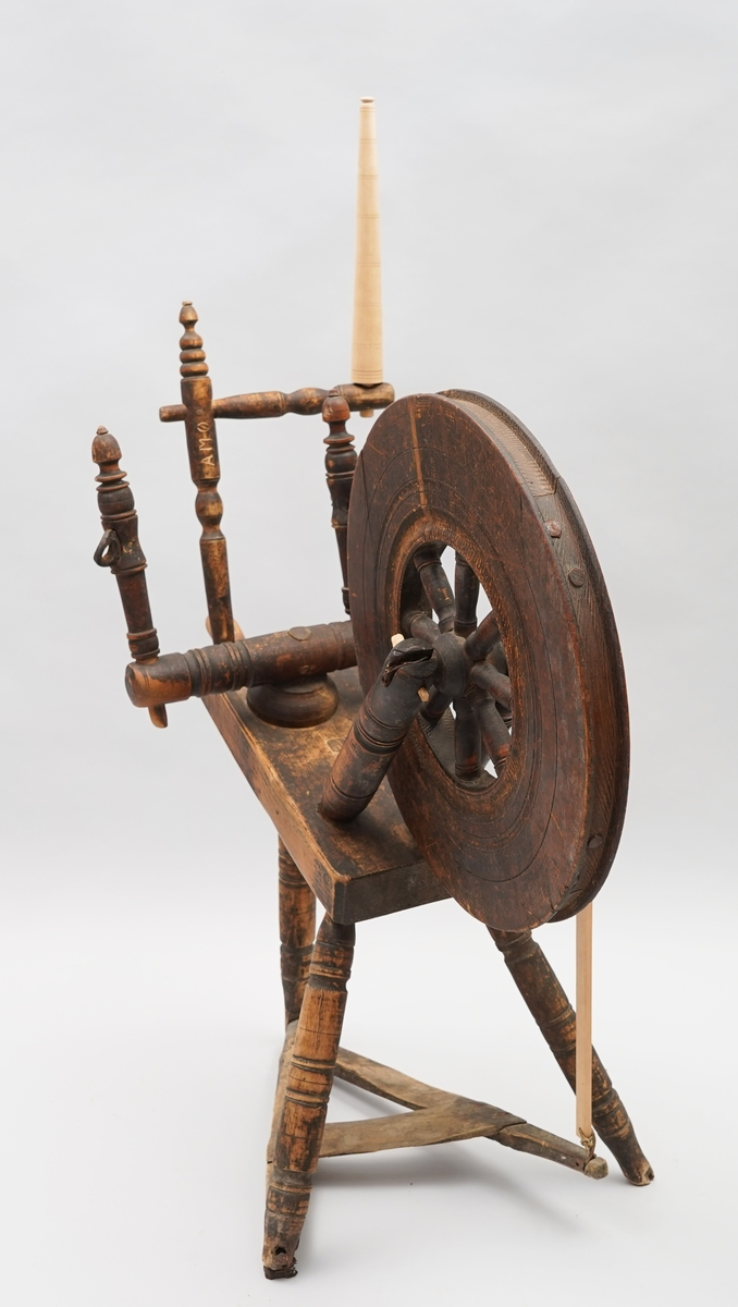 Hjulrokk med skrått, enkelt bryst. Tre bein. Smal trøe i enkel utforming. Rokkehjul med brei kant av massivt tre ytst og med åtte, korte spilar. Med rokkearm og rokkehovud. Øvste del av rokkehovudet og trøespila (veiva) er laga på museet i 1980 utan modell. På arm rissa inn A M Ø , mogeleg sekundært. Utan tein. Det har vore tein, men den er borte nå. Svirosedekor på kvar langside av bryst.