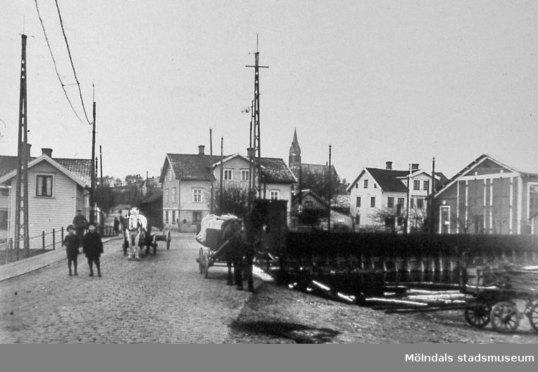 Vy över Mölndals Bro mot bebyggelse vid Göteborgsvägen i Mölndal. Fotografi taget på 1910-talet? På bron ses hästsjutsar. Till höger ses spårvagnsgaraget och i bakgrunden Fässbergs kyrka. AF 3:27.