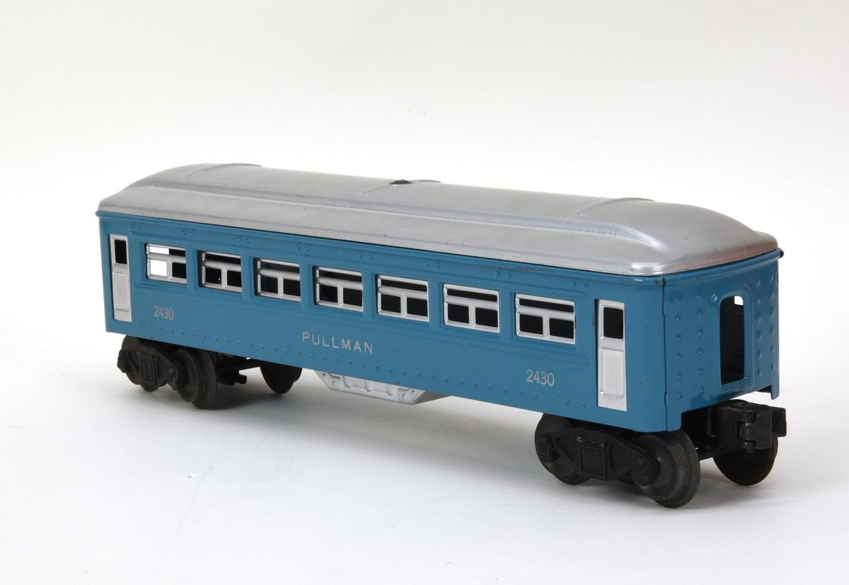 """Personvagn av plåt med boggier och elektriska vagnskopplingar (:5). Vagnen är blå med tak, dörrar och fönster i silver. Fönstren är täckta med en lätt frostad plastremsa och vagnen saknar inredning. På sidorna under fönsterraderna finns """"2430"""" och """"PULLMAN"""" tryckt i silver. Taket är fäst med en skruvad klammer i korgen som är pressad och bockad ur ett plåtstycke. Boggierna är vridbara och har varsin liten strömupptagare för att aktivera den elektromagnetiska vagnkopplingen.  Till vagnen hör en förvaringsask i kartong (:6) med tillverkarnamn och modellnummer tryckt i blått mot orange botten."""