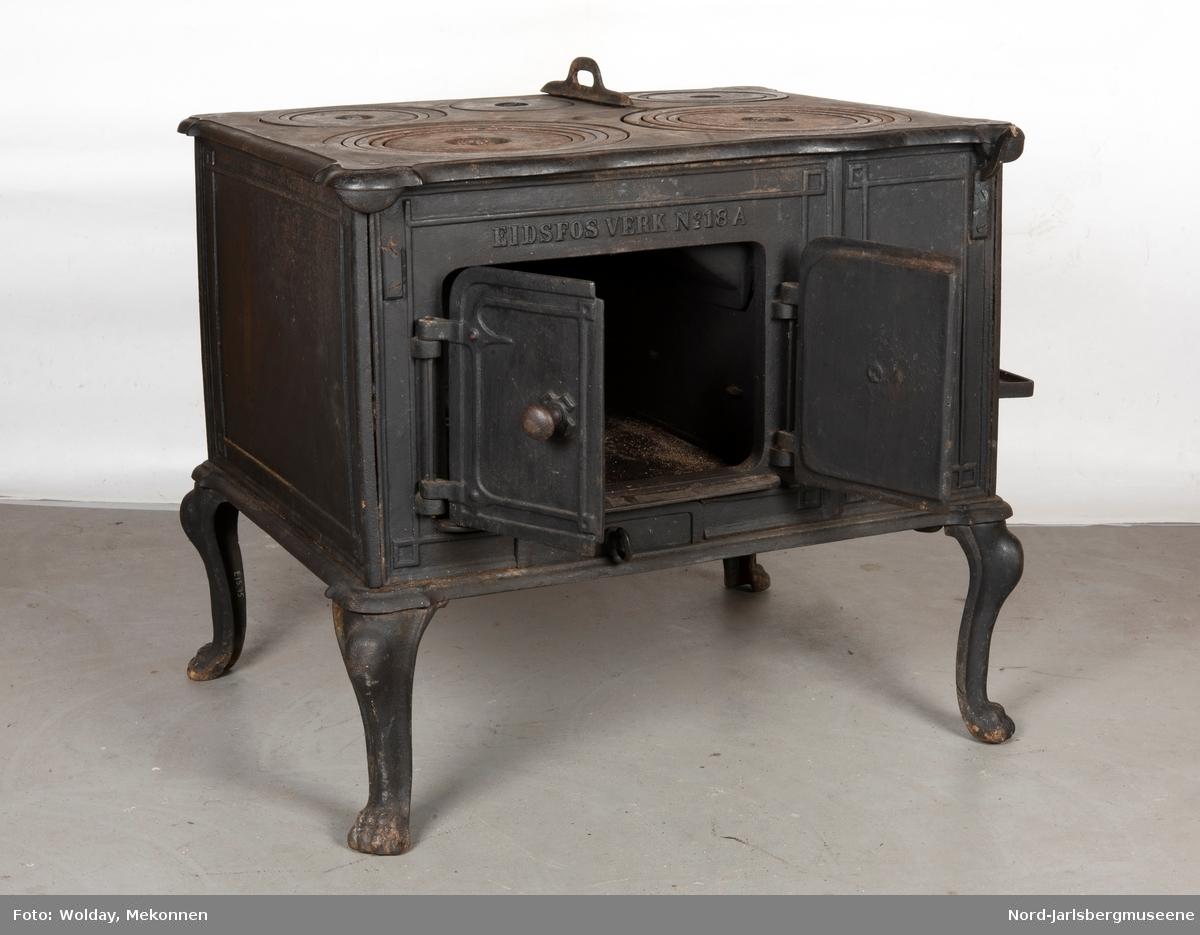 Stor, firkantet komfyr med dobbel ovnsdør til stekeovn? med støpte knotter. Enkel dekor (stilisert art nouveau). Sidedør til stekeovn. Fem kokeplater.  Bena svungne.