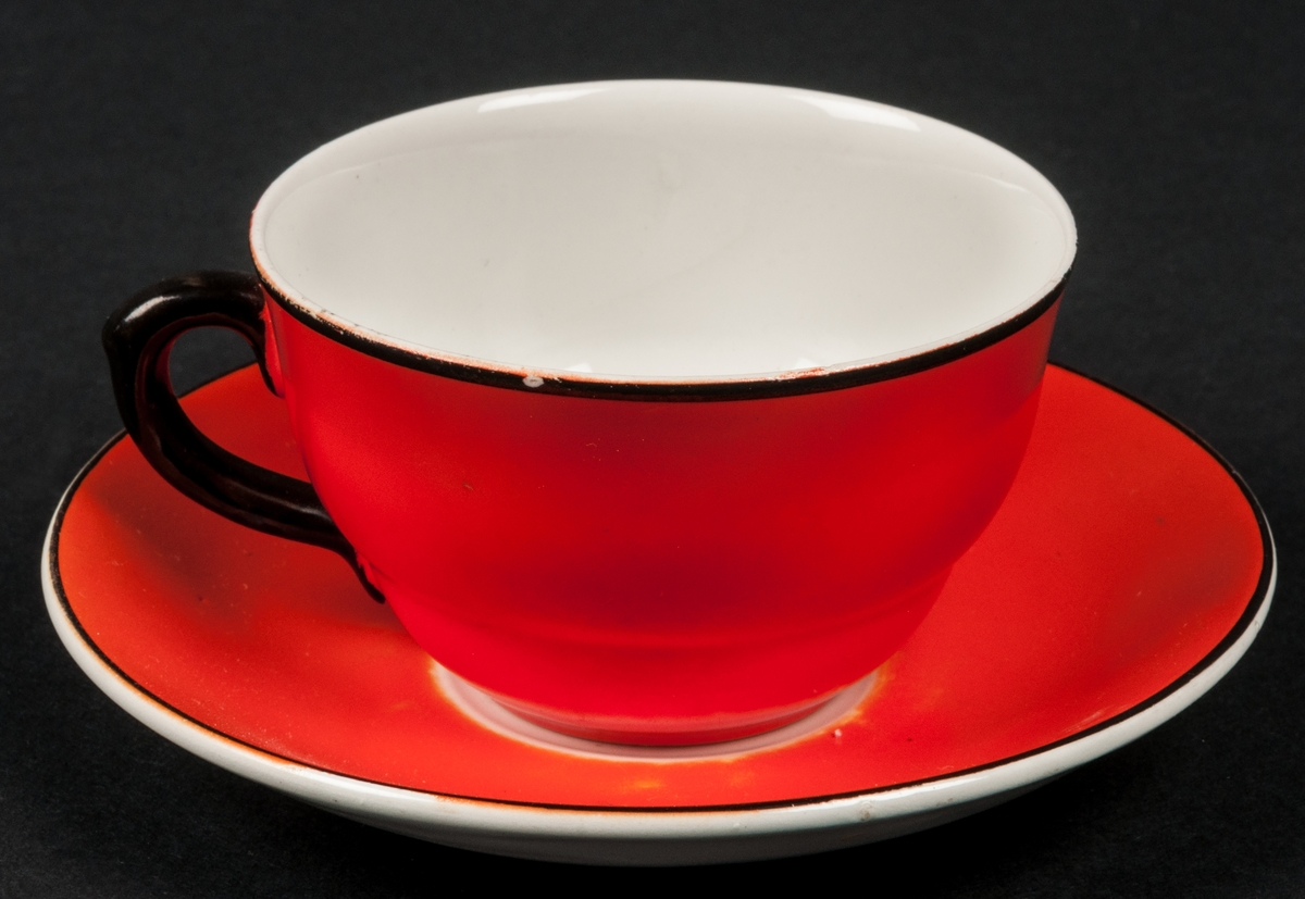 Kaffekopp med fat. Röd glasyr med svarta kanter och svart hänkel. Insidan av koppen vit, samt undersidan av fatet.
