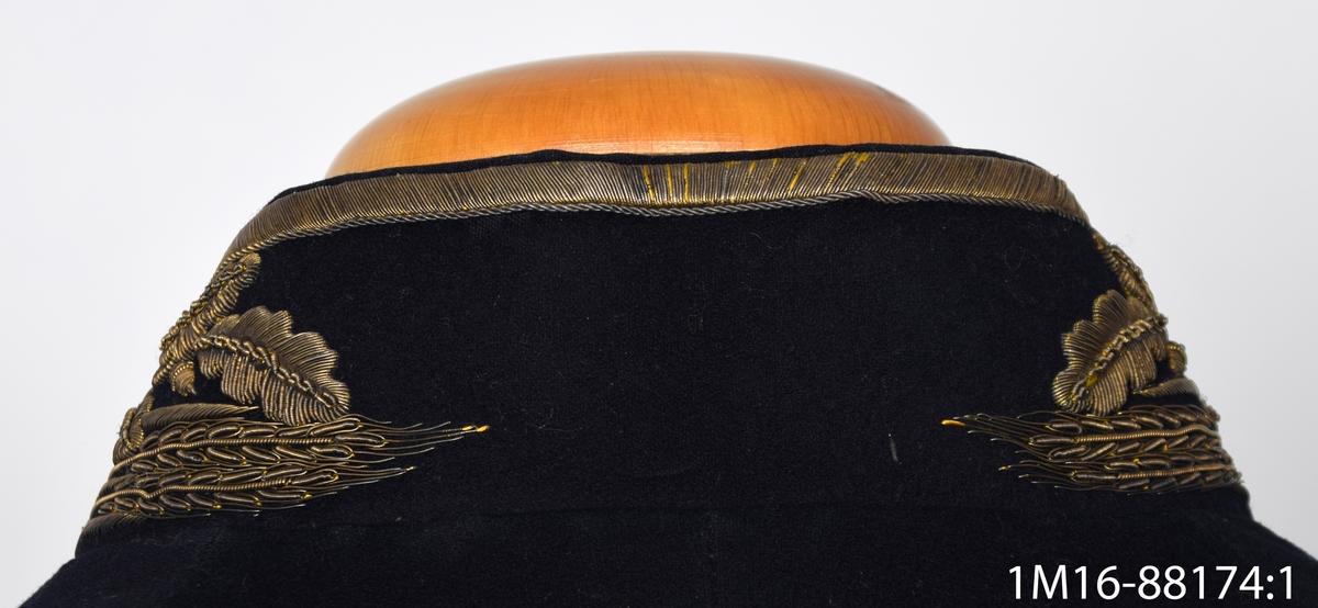 """Uniformsrock, till lantmäteriuniform för kommisionslantmätare, av mörkblått kläde, åtta mässings knappar framtill med en triangel omgiven av en öppen krans av eklöv och ekollon. Rocken knäpps inte med knapparna utan med två hyskor framtill. Ståndkrage med metalltrådsbroderi med mönster i form av eklöv, ekollon, kornax samt trianglar. Två mässings knappar på vardera ärm. Rocken är midjelång framtill men betydligt längre baktill. Skjört baktill samt sju mässings knappar, två ficklock utan fickor. Rocken är fodrad med mörkblått siden, i ärmarna är fodret av beiget siden. En innerficka på rockens vänstra sida. Etikett: """"G.U. Heurlin & Co. Stockholm"""", emblem med en en sköld och djur."""