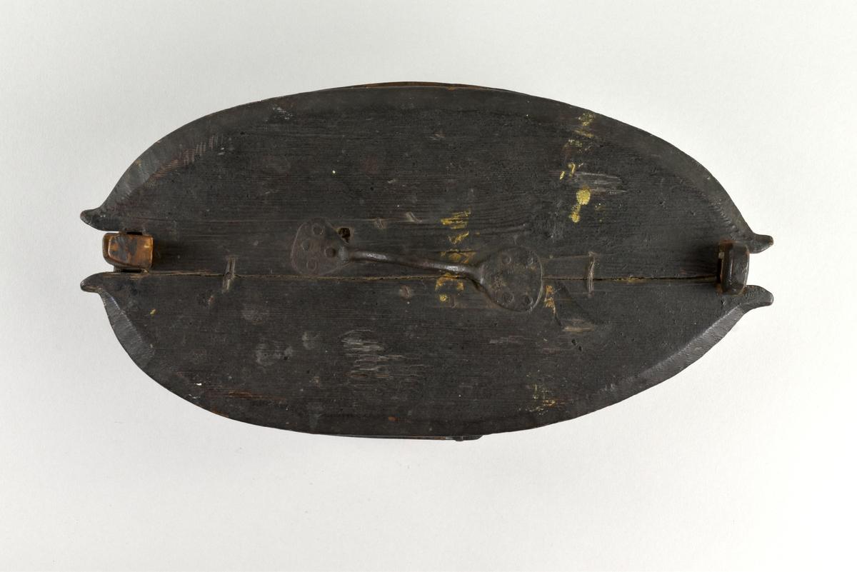 Oval äska med lock i svepteknik. Målat i mörkgrönt. Smitt handtag av järn på locket, handtaget fäst i ett järnbleck på undersidan . Lockets undersida målad i en grågrön färg.
