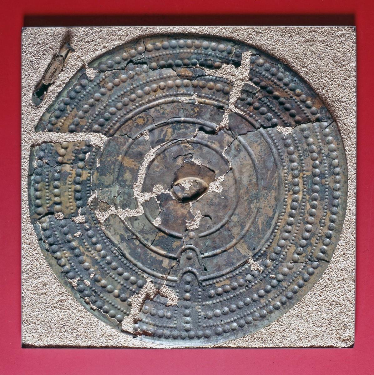 Skölden är fragmenterad, ca 5 procent av sköldplåten saknas. Omkretsen är intakt. Längd ca 688 mm, bredd ca 672 mm och tjocklek ca 0,5 mm. Sköldens vikt, inklusive handtaget, uppgår till 1349 gram.  Sköldkanten är jämnt rundad och väl omvikt mot framsidan, ursprungligen runt en kärna av tenn av vilken rester är bevarade. Kanten är avbruten på 12 ställen. Kanttjocklek: ca 5,8 mm. Spår av kantlagningar i form av borrade hål förekommer på tre ställen; i två fall på ömse sidor om en sprickbildning, i det tredje som ett enstaka hål. Inga spår av lagningsbleck eller tråd kan iakttas. I sköldens centrala del finns tre vulster med flackt bågformade tvärsnitt. Bredd: 10,8-11,6 mm, djup 1,9-2,9 mm. Sköldbucklan, som har haft oval form, är bevarad till ca 75 procent. Då den ena spetsen saknas uppskattas längden till ca 85 mm. Bredden är 51 mm men eftersom bucklan är delvis deforme-rad har den sannolikt varit något bredare. Höjden varierar mellan 7,9-9,1 mm till följd av att plåten är mycket tillknycklad. Sköldhandtaget som lossnat från plåten är brett med flack välvning. Längd: 152 mm. När handtaget bröts loss uppstod skador på såväl detta som sköldplåten. Greppets längd är 126 mm, bredd 23,9-26,6 mm och tjocklek 11,3-16,7 mm. Tvärsnittet är oregelbundet där sidorna är hårt nerhamrade med skarpt markerad vinkel mot ovansidan. Betydande rester av handtags-fyllning, förmodligen av bly, är bevarade. Sköldhandtaget har varit fastsatt med två nitar på varje sida. Ingenting tyder på att det skulle ha funnits nitbleck. Spår av drivning kan iakttas på sköldens baksida i form av linjer, ca 15 mm långa och 1-2 mm breda.