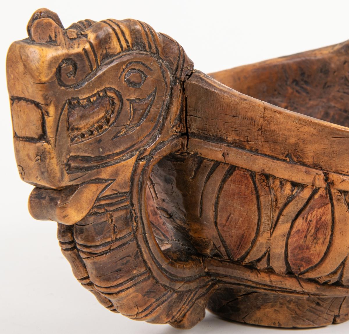 """""""Kåsa"""", """"bröllopsskål"""", av masurbjörk med reliefdjurhuvuden på handtagens övre del, nedre delarna repstavsartade. Runt yttersidans buktning är utskuret bucklor med lodräta skåror. Här finns spår av röd färg.  Jfr. silverkåsornas form. Märkt: IAS 1638. Dalarna, Orsa socken."""