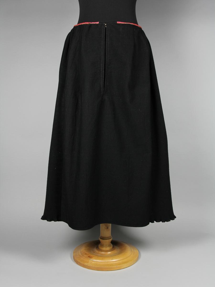 Kjol till Gagnefsdräkten. Svart kjol av ylle plisserad i ca 2 mm djupa veck. Framtill på kjolen är ett stycke slätt och oplisserat. Mot linningen är kjolen veckad i mycket små veck och kanten omsluts av ett en centimeter bredd färglatt mönstervävt band. Kjolens stängs med en hyska och hake mitt fram ovan ett sprund. Sprundet är kantat på insidan med ett vävt randigt band. På kjolens högra sida finns en ficka osynligt insydd i en söm. Kjolen är sydd med raksöm på symaskin och för hand.