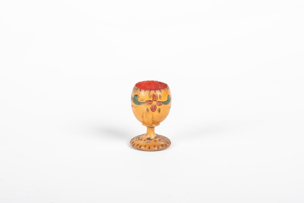 Eggeglass i tre som er dreid. Den har malt blomstedekor, og innbrent tekst og mønster. Den er malt rød på innsiden.