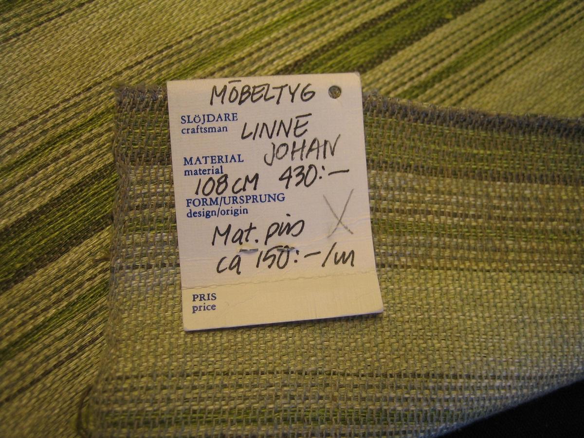 """Ett stadigt möbeltyg i tuskaft. Tyget är randigt med en smala och breda ränder i grönt, vitt och  gråttt. Varpen är brunt bomullsgarn. Inslaget är lin.   En lapp är fastsatt med texten:""""LÄNSHEMSLÖJDEN SKARABORG SKÖVDE-LIDKÖPING"""" på ena sidan och """"Möbeltyg Linne Johan 108 cm, 430:- Mat.pris: ca 150:-/m"""" på andra sidan."""