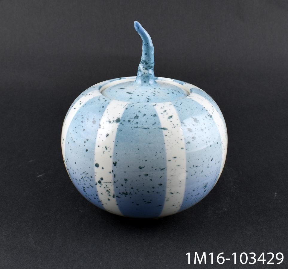 Urna med lock, klotformad. Locket har en kvistliknande knopp. Urnan liknar en pumpa till formen. Dekor, stänkmålad och spraymålad. Drejad. Märkt: Sanna Öhlén, Klockaregården.