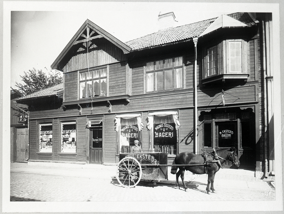"""Enligt tidigare noteringar: """"Magnus Ekstedts Bageri Kilbäcksgatan 3 Uddevalla. Exteriör, framför bageriet hästdragen kärra för brödutköring""""."""