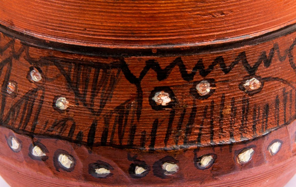 Skål av trä, svarvad och med täljda partier, två handtag, bukig, av bolletyp. Målad röd och med ornament tecknade med svarta linjer och vita punkter.