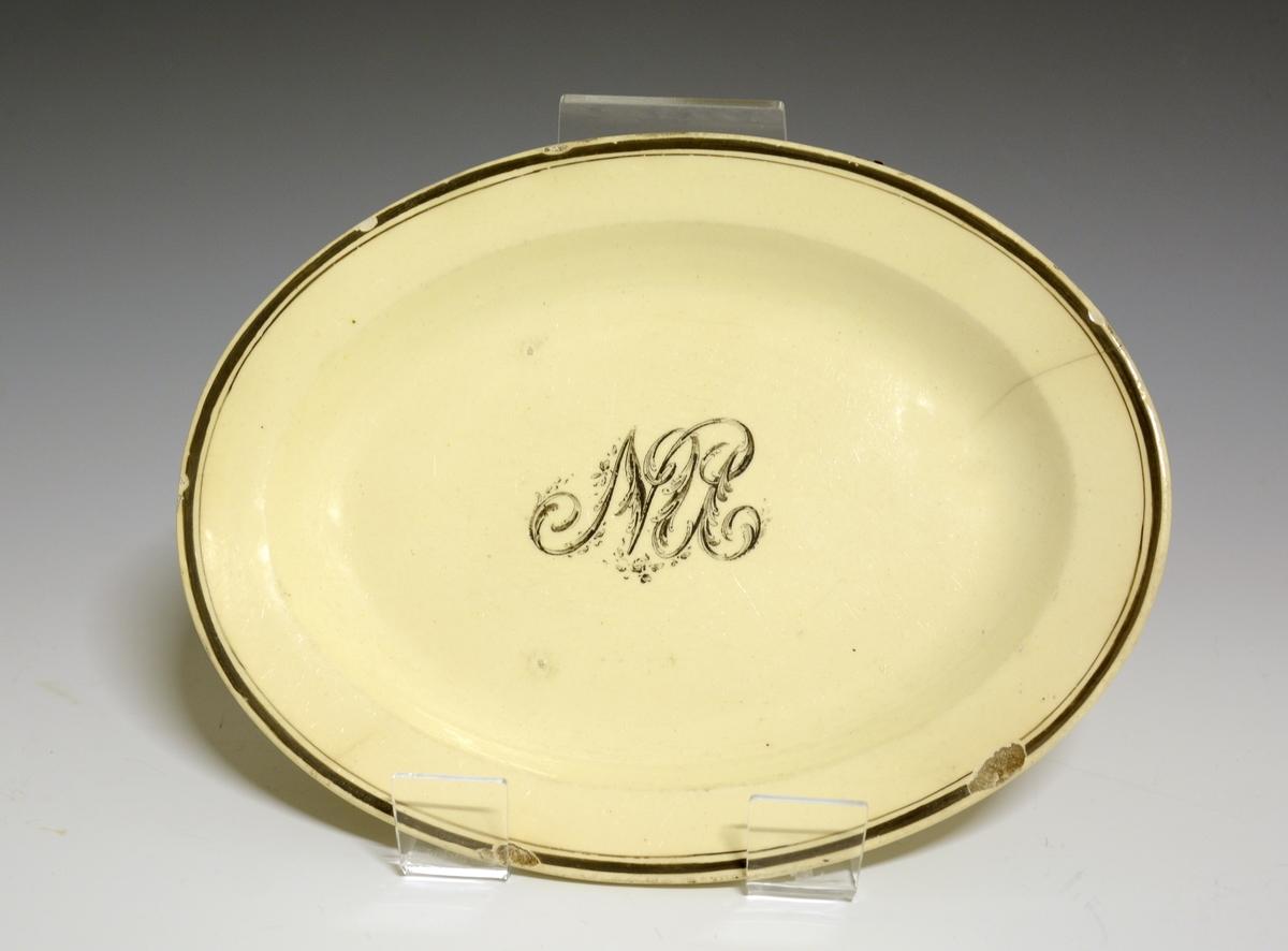Lite, ovalt fat av stentøy med gulhvit glasur. I speilen et monogram med bokstavene NU. Ytterst på fanen en bredere og en smalere sort strek.