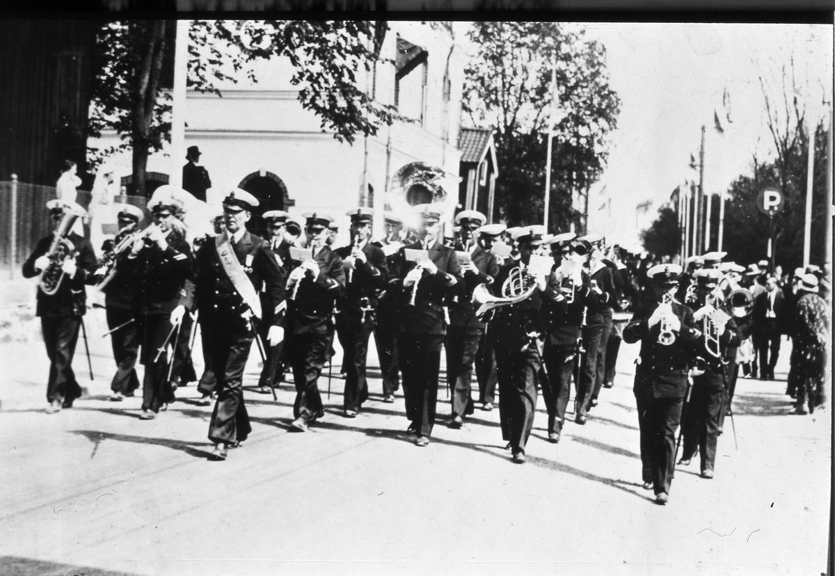 Flottans Musikkår, under ledning av Ivar Widner, paraderar på Strandvägen. Till vänster ses brandstationen. Riksdagens 500-årsjubileum firas i Arboga. Arbogautställningen pågår samtidigt.