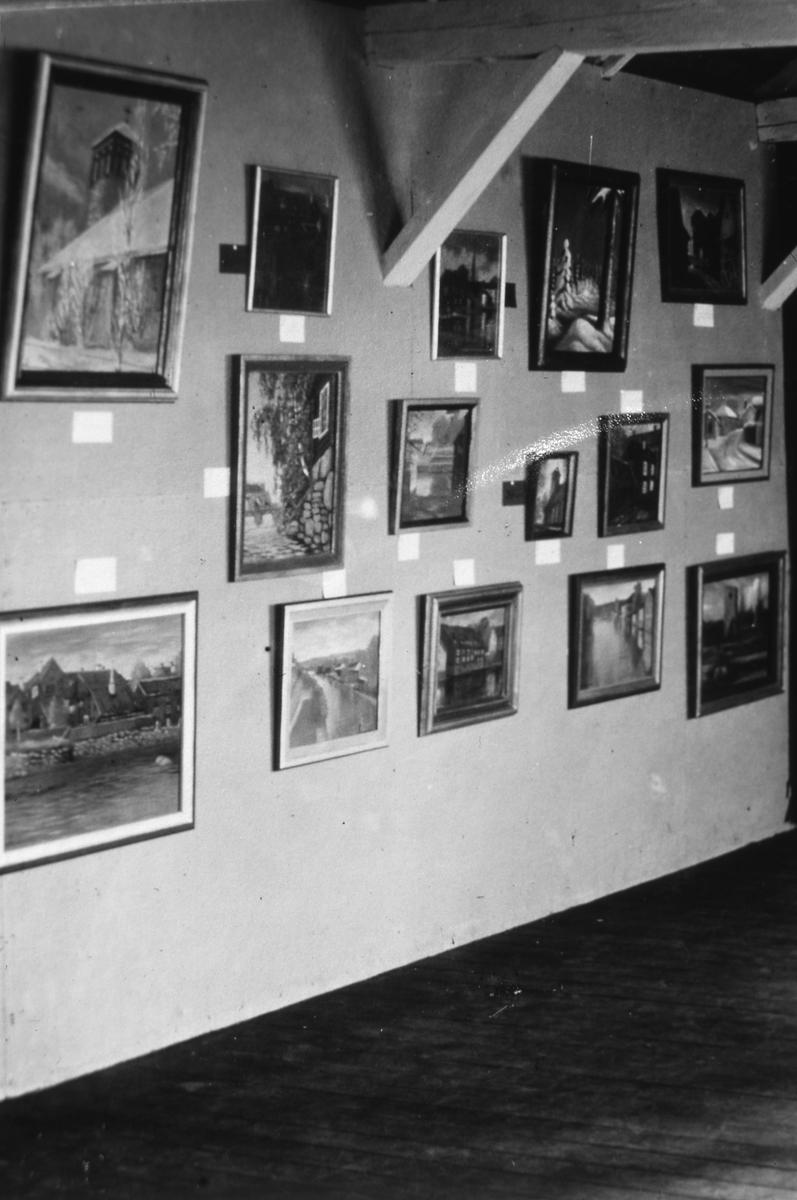 Konstnärinnan Elin Höglunds debututställning, på Kägelbanan under Arbogautställningen. Inramade tavlor i tre rader hänger på en vägg.