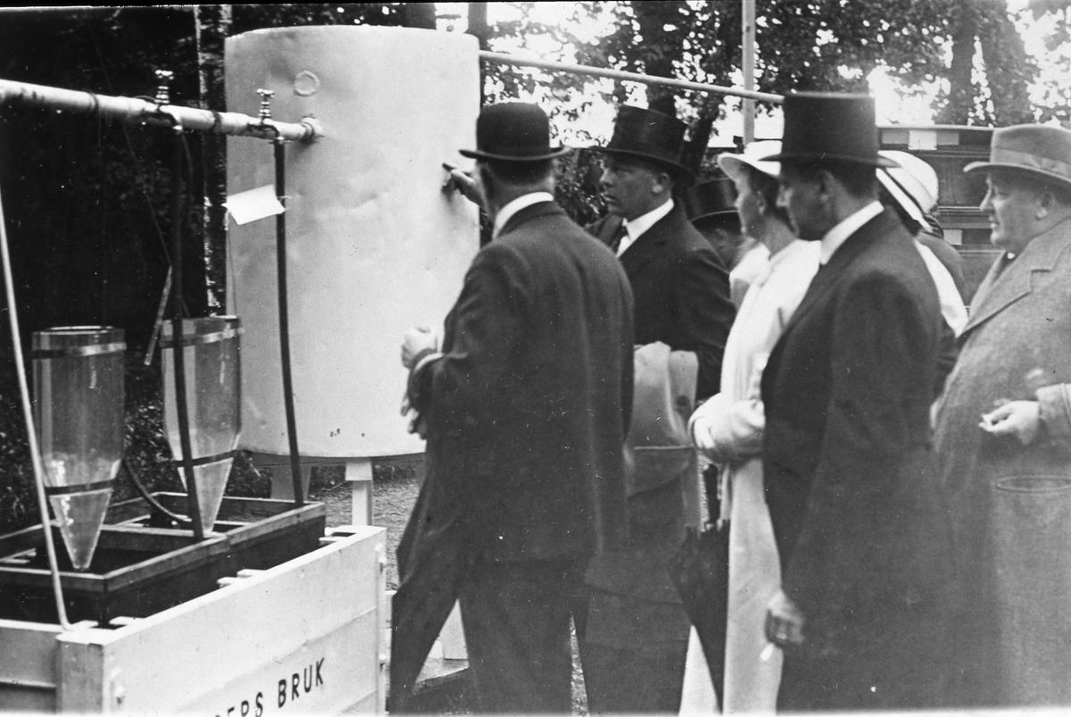 Arbogautställningen pågår. Här är Jäders bruks del av utställningen. Herrar och damer i hattar studerar en installation. En herre förklarar hur det hela fungerar.