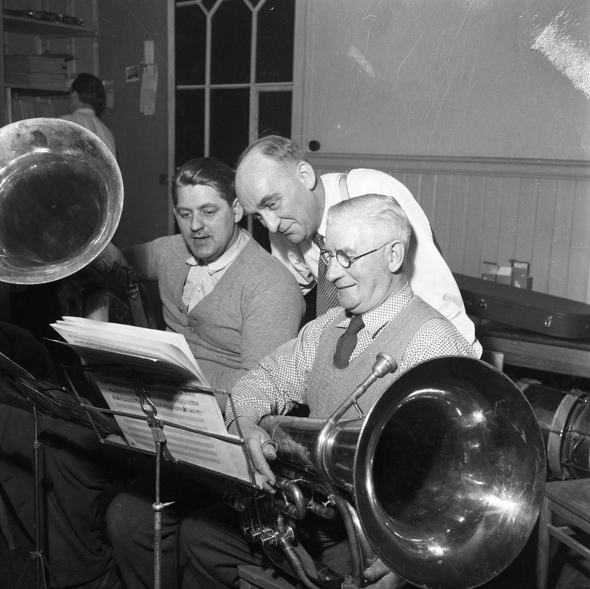 """Arboga Blåsorkester repeterar med musikdirektör Yngve Kjerrgren från I 3 Örebro som instruktör. 1950-talet Männen med tuborna heter Nils Jönsson (till vänster) och Harald """"Hammars-Harald"""" Andersson (till höger)  Män med musikinstrument, notställ och noter."""