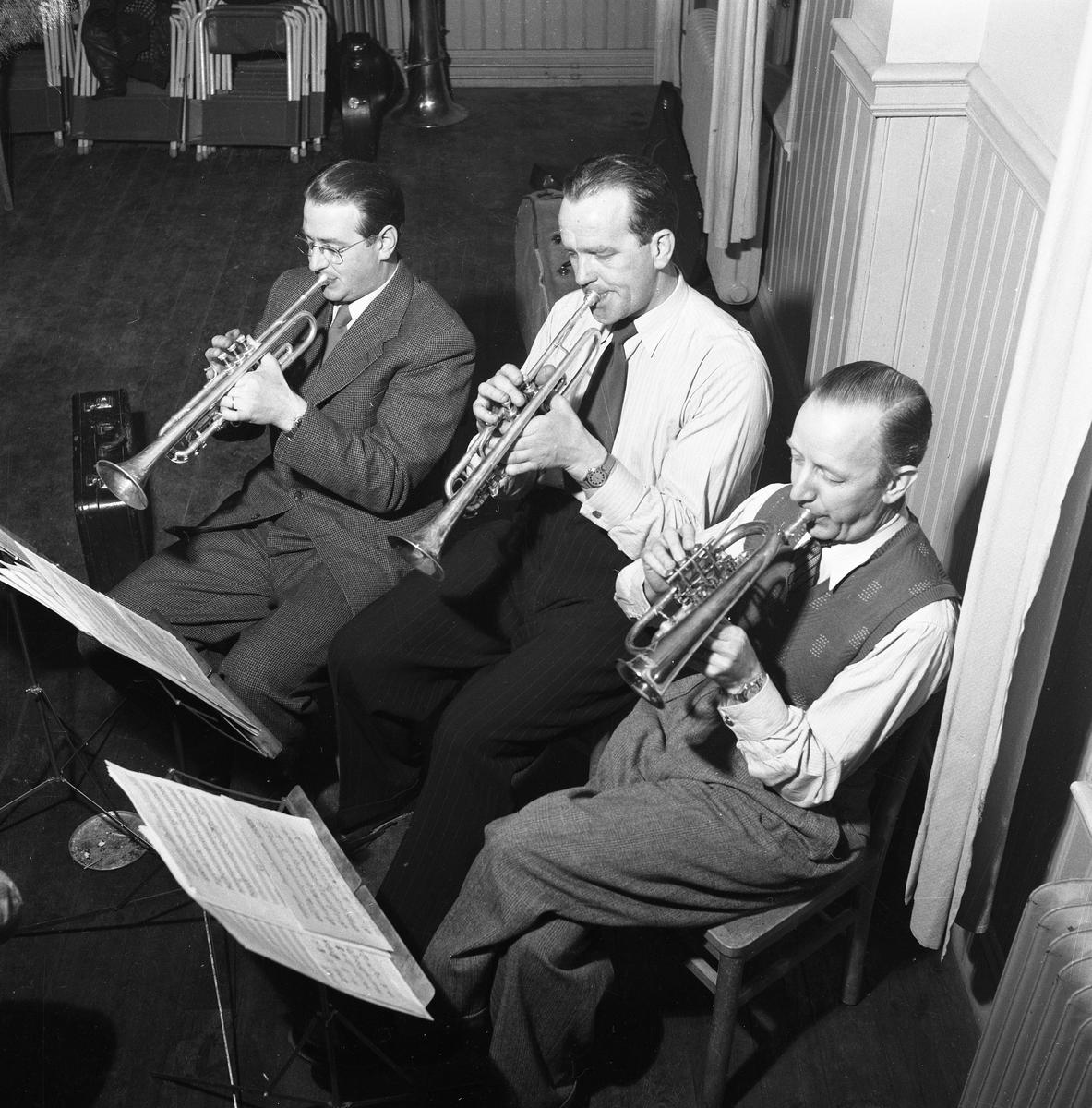 Arboga Blåsorkester repeterar 1950-talet Tre män spelar trumpet. Ingen är identifierad.  Män med instrument, notställ med noter