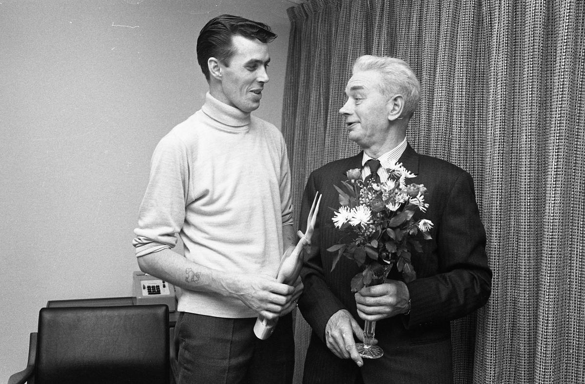 Det är pensionärsavtackning hos Arboga Maskiner. Den äldre mannen, iklädd kavaj och slips, håller en blombukett i en vas. Den yngre mannen, iklädd polotröja, håller i en snidad gasell i trä, förmodligen en gåva till pensionären.