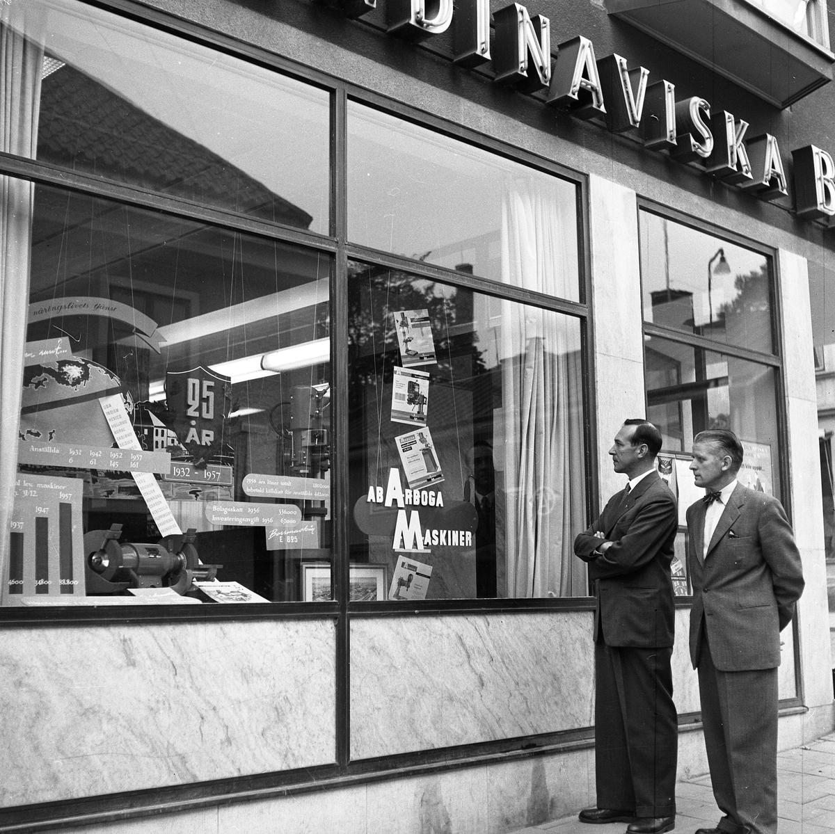 Arboga Maskiner 25 år Två kostymklädda män ser på en utställning om Arboga Maskiner. Utställningen visas i fönstret hos Skandinaviska Banken. Banken ligger i hörnet Järntorgsgatan - Nygatan, männen står på Nygatan. Direktör Hroar de la Cour till vänster och disponent Torsten Brüde till höger. Arboga Maskiner startade 1932 och tillverkar borr-och slipmaskiner.  Denna bild finns med i Reinhold Carlssons bok Arboga objektivt sett.