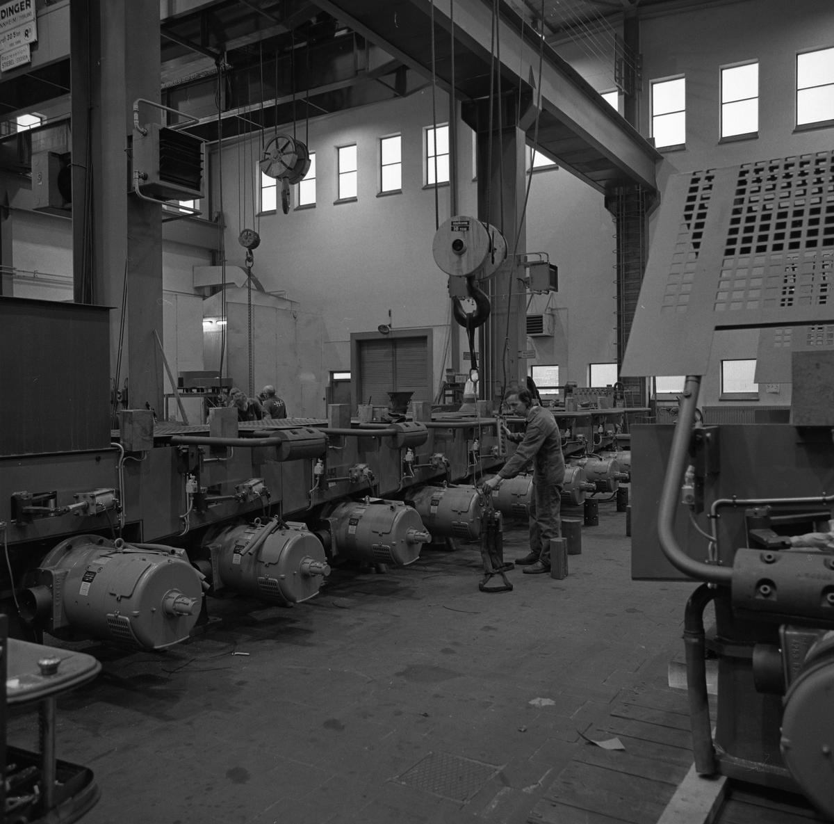Arboga Mekaniska Verkstad, interiör. Meken. Några män, iklädda overall, arbetar i en fabrikslokal. Det finns traverser i taket och många maskiner på golvet.  25 september 1856 fick AB Arboga Mekaniska Verkstad rättigheter att anlägga järngjuteri och mekanisk verkstad. Verksamheten startade 1858. Meken var först i landet med att installera en elektrisk motor för drift av verktygsmaskiner vid en taktransmission (1887).  Gjuteriet lades ner 1967. Den mekaniska verkstaden lades ner på 1980-talet. Läs om Meken i Hembygdsföreningen Arboga Minnes årsbok från 1982.