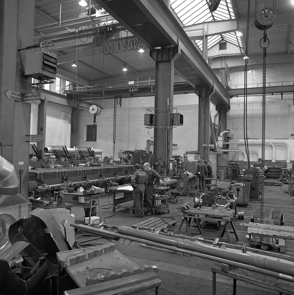 Arboga Mekaniska Verkstad, Meken, interiör. Några män, iklädda overaller, arbetar med maskiner i en stor fabrikslokal. Det hänger traverser i taket.  25 september 1856 fick AB Arboga Mekaniska Verkstad rättigheter att anlägga järngjuteri och mekanisk verkstad. Verksamheten startade 1858. Meken var först i landet med att installera en elektrisk motor för drift av verktygsmaskiner vid en taktransmission (1887).  Gjuteriet lades ner 1967. Den mekaniska verkstaden lades ner på 1980-talet. Läs om Meken i Hembygdsföreningen Arboga Minnes årsbok från 1982.