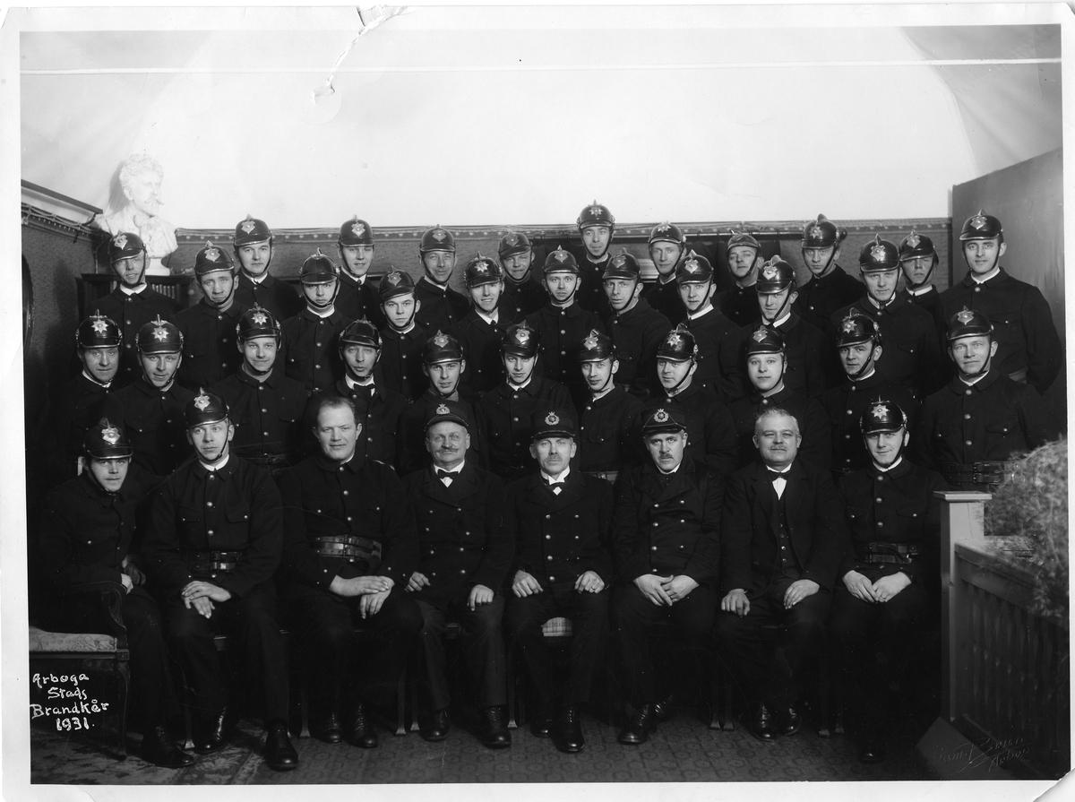 """Arboga stads brandkår, gruppfotografi Trettinio män uppradade inomhus. Alla bär uniform utom en som är klädd i kosym. De flesta har hjälm på huvudet, några har skärmmössa.  Texten """"Arboga stads brandkår 1931"""" är skrivet, i vitt, i bildens nedre vänstra hörn. I nedre, högra hörnet, är """"Sam Brun Arboga"""" präglat."""