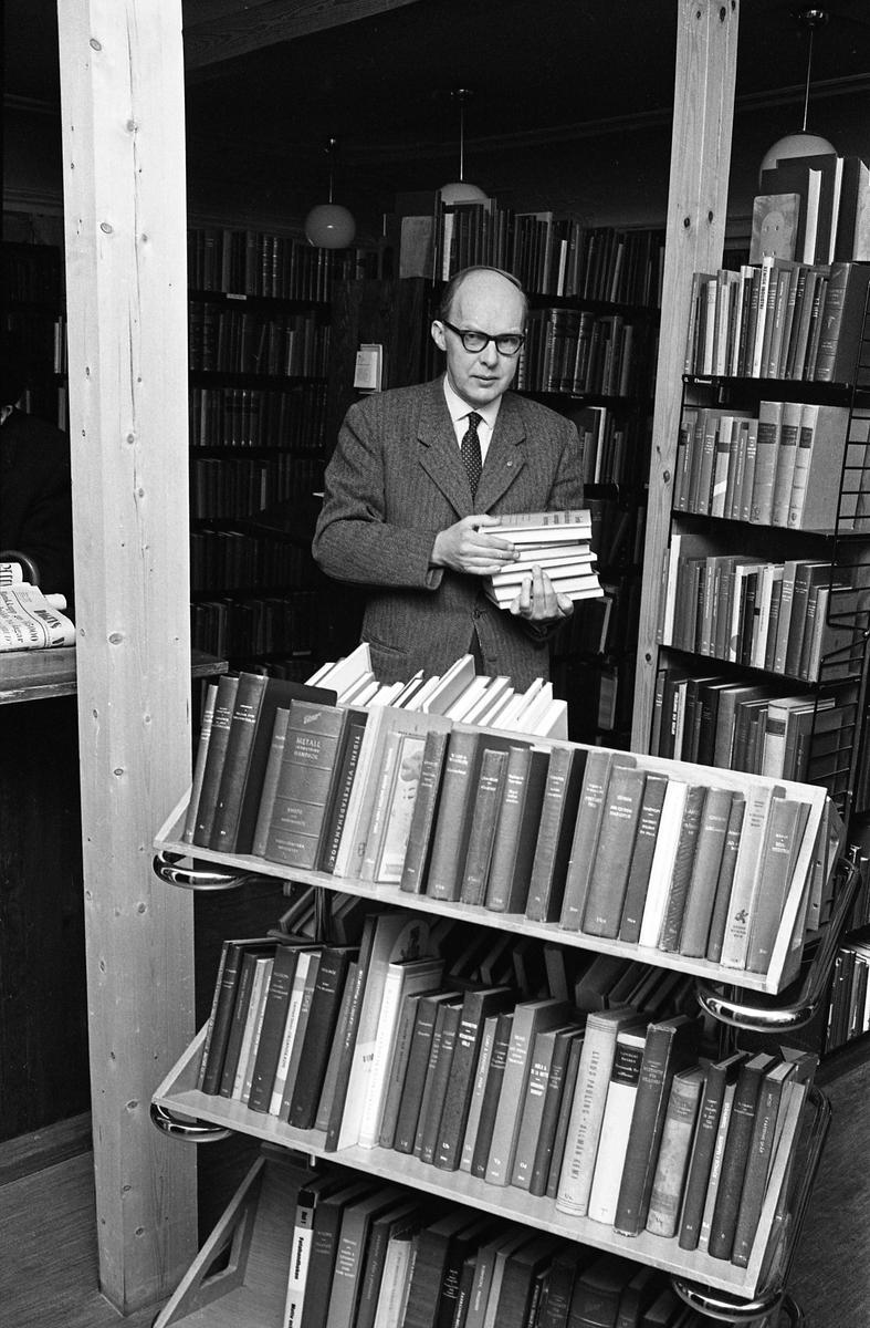 Arboga Stadsbibliotek, interiör. Man med böcker, omgiven av bokvagn och bokhyllor. Mannen är Östen Bengtsson, chefsbibliotekarie. Biblioteket låg i