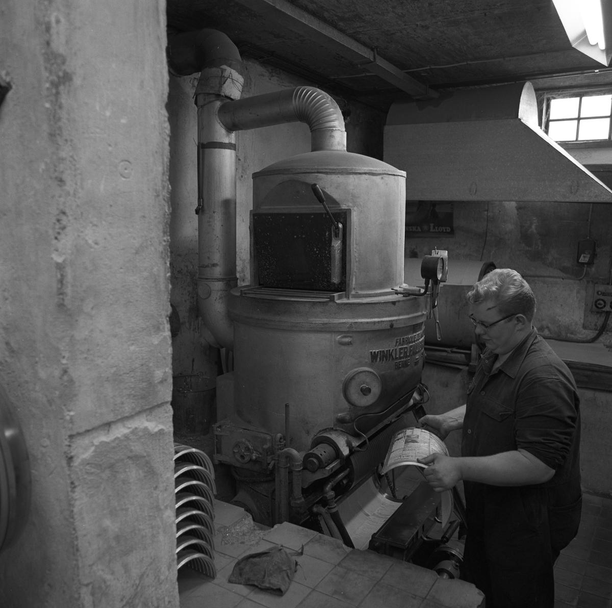 Arboga Tidning, personal och interiör. En man, iklädd overall, arbetar vid en maskin. Han håller i en plåt som används för att trycka en tidningssida. Flera plåtar syns till vänster i bild. Mannen vistas i en källarlokal.
