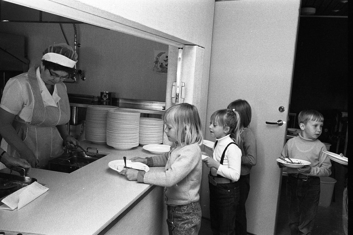 """Barn från lekskolan är på besök i skolan. Här står de i kö i skolbespisningen. Bakom luckan står en """"mat-tant"""" med förkläde och mössa. Barnen har tallrikar i händerna."""