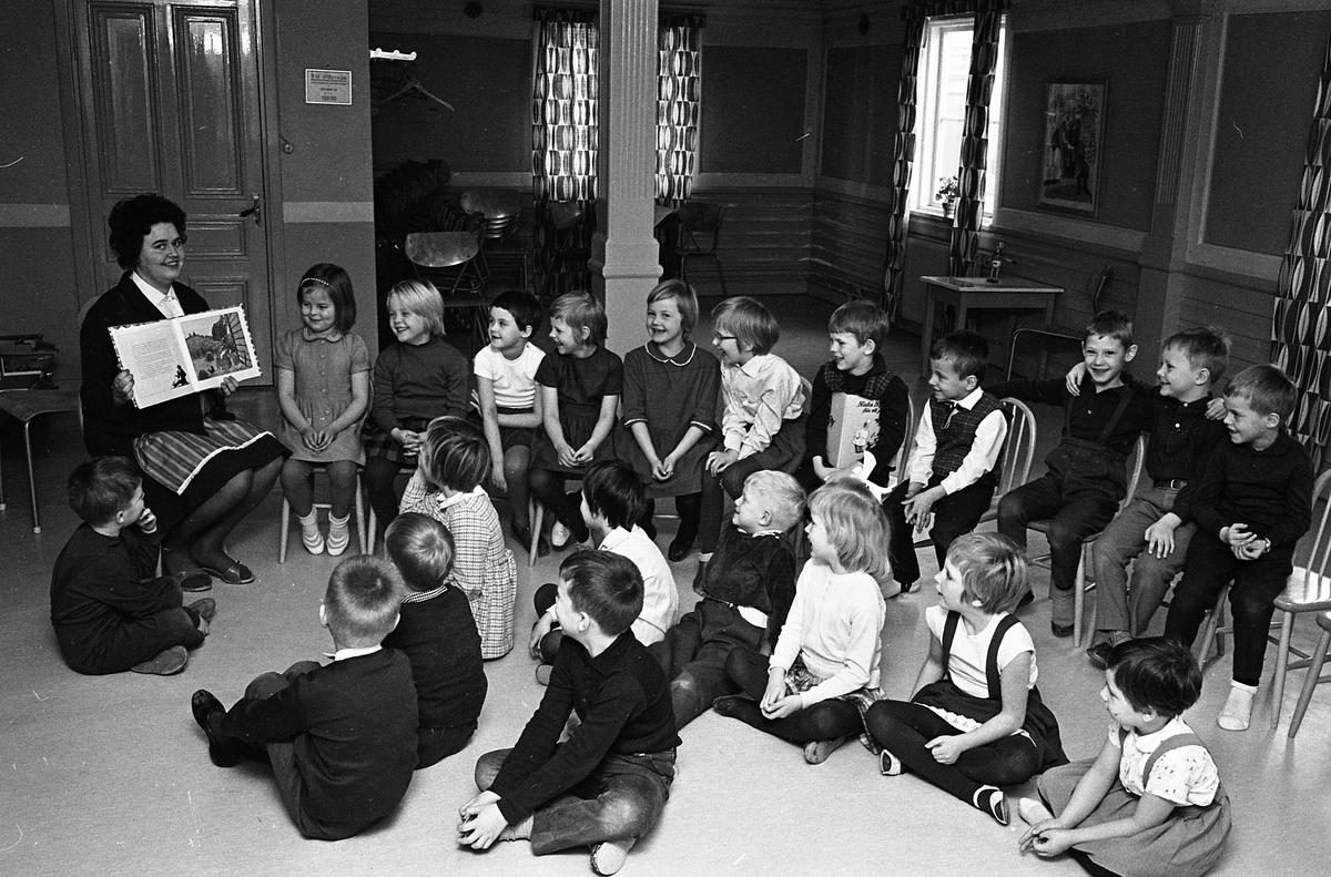 """Barnträdgård, Arbetarnas Bildningsförbund, ABF, på Stadsgården. En """"fröken"""" visar bilder i en bok. Barnen sitter på stolar eller på golvet."""