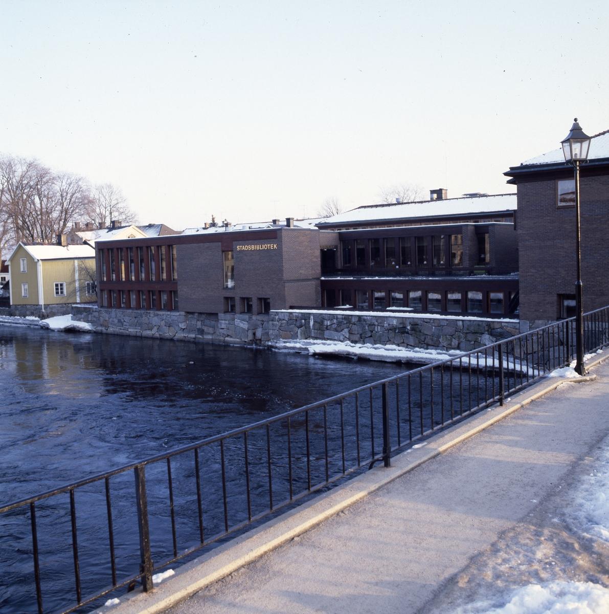 Biblioteket sett från Kapellbron. Det är vinter och snö. Arbogaån.