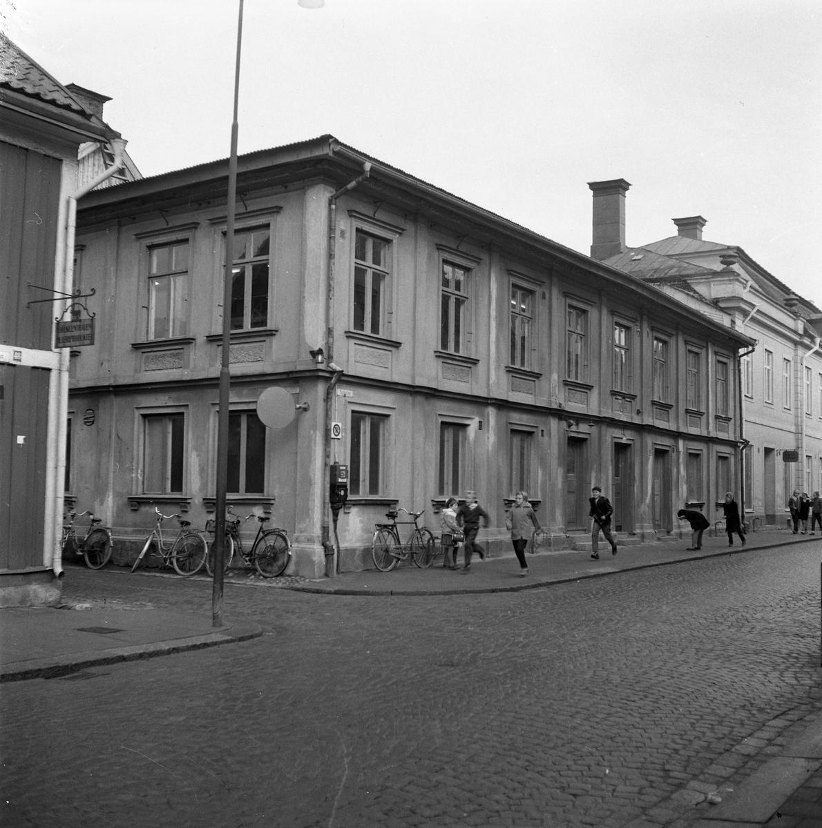 """Biblioteket ligger i den här fastigheten på Nygatan. Huset är """"Gamla Gästis"""". Skolbarn kommer springande på trottoaren. Flera cyklar är parkerade utanför biblioteket. På huset längst till vänster hänger en skylt med texten """"Mjölkcentralen. Mejeriprodukter""""."""