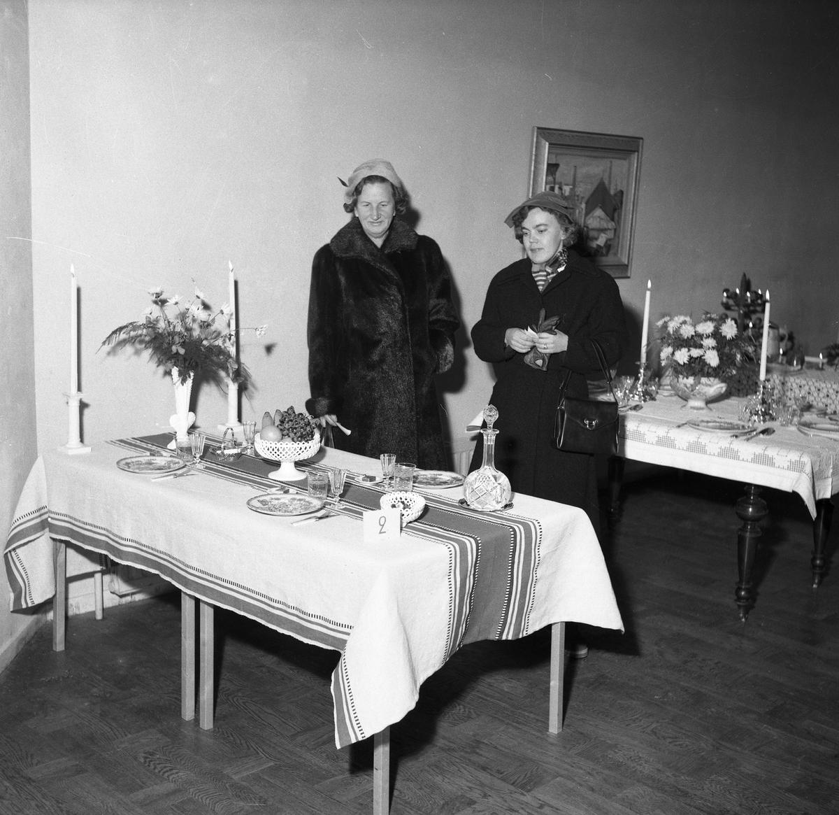 Utställning med olika dukningar visas på Folkan/Medborgarhuset. Här är det dukat med frukt och karameller samt en karaff. Porslin, ljusstakar och en vas med blommor finns på bordet. Två kvinnor ser på utställningen, den ena är klädd i päls och den andra i kappa.