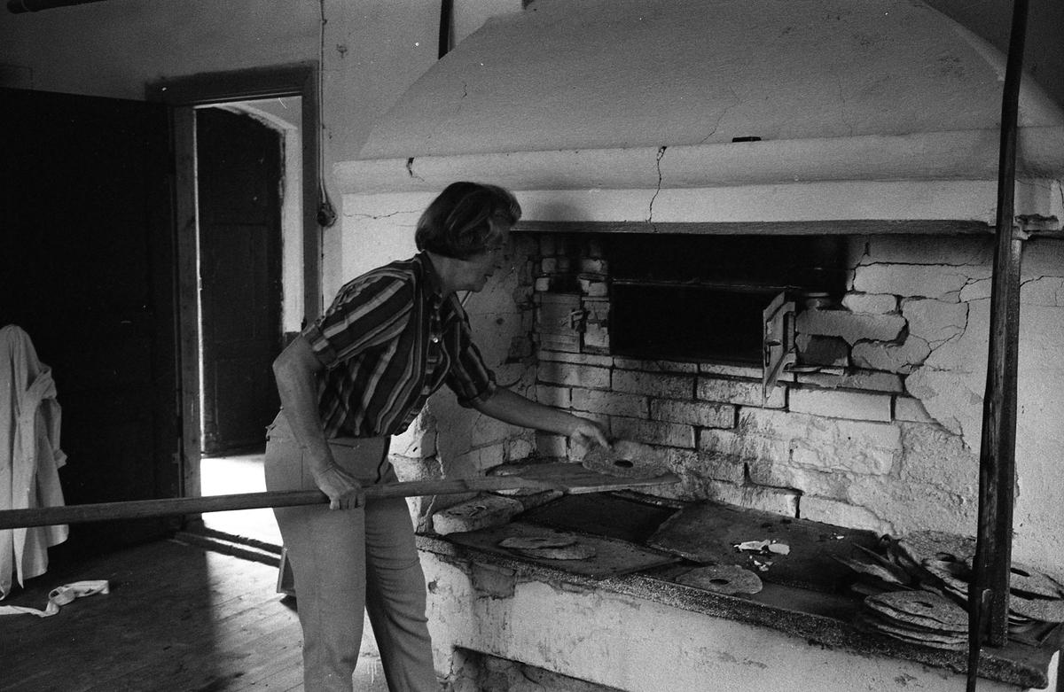 Brödbakning vid Jäders bruk. En kvinna i en bakstuga/bagarbod. Hon håller i en brödspade med knäckebröd. Vid det ena fönstret finns ett bakbord med brödkavel, mjölpåse, bunke och brödkavel.