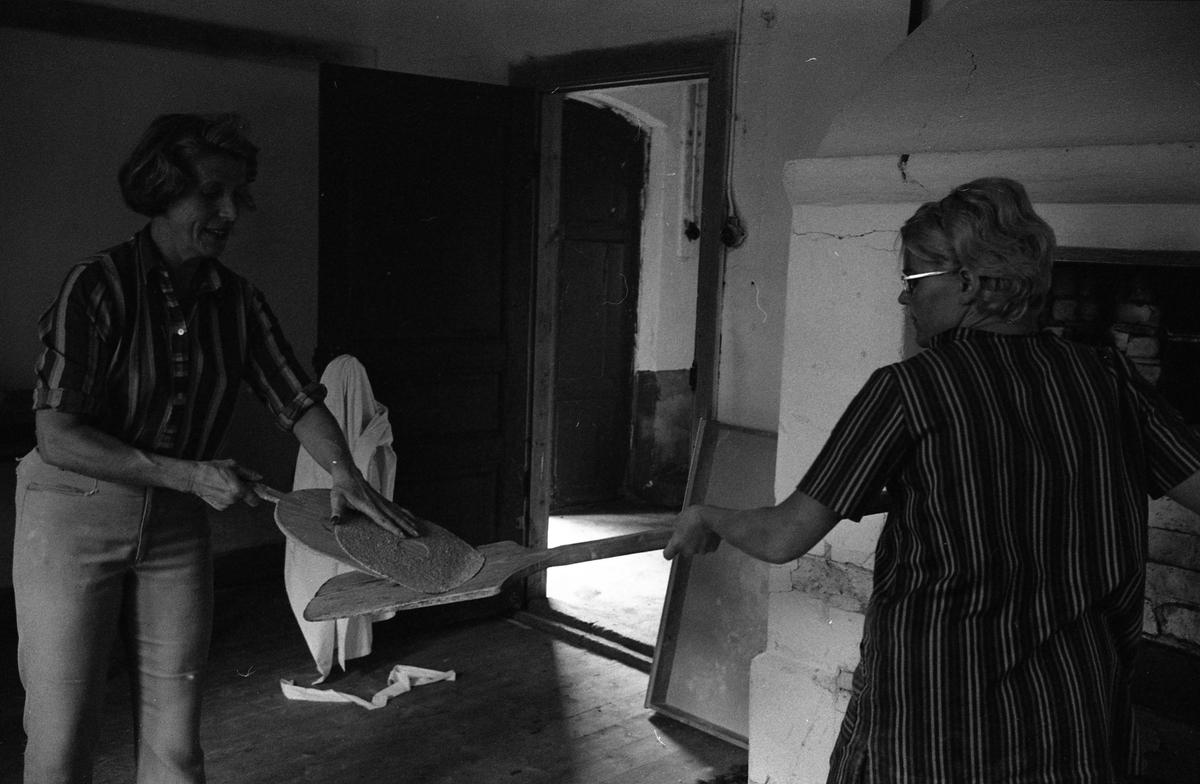Brödbakning vid Jäders bruk. Två kvinnor vid en bakugn i en bakstuga/bagarbod. En kvinna håller i en brödspade. Möjligen bakar de knäckebröd. Vid det ena fönstret finns ett bakbord med brödkavel, mjölpåse, bunke och brödkavel.