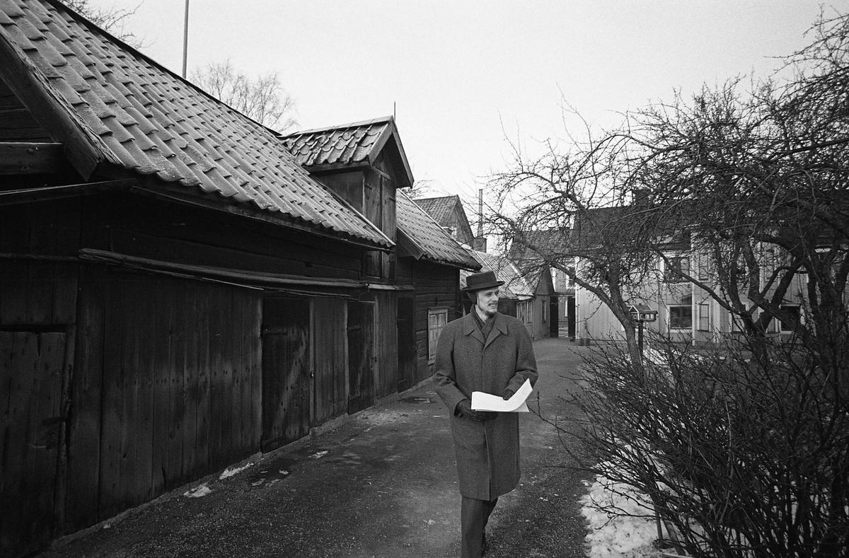 En man, iklädd överrock och hatt med öronlappar, går i kvarteret Tullnären med papper i handen. Ett förråd till vänster och ett boningshus till höger. Fotografens anteckning: Dokumentation av fastigheter i kvarteren söder och norr om ån. Bilder och beskrivning finns på Arboga Museum.